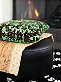 A cushion and a blanket on a leather stool