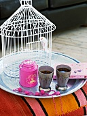 A bird cage and tea cups on a tray