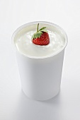 A strawberry in a cup of yogurt