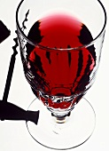 A glass of red wine and a corkscrew (transmitted light)