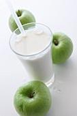 Milchglas mit Strohhalm und drei grüne Äpfel