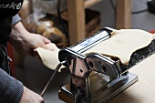 Woman Cranking Pasta Machine; Making Fresh Pasta