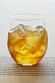 Cocktail mit Eiswürfeln und Zitronenschale