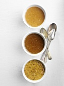 Three different types of mustard in bowls seen from above