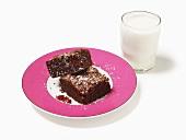Kirsch-Schokoladen-Brownies auf Teller, daneben Milchglas