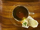 Mulberry tea in a glass cup, seen from above with a tea bag on the saucer