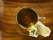 Mulberry Tea (Maulbeertee) in Glastasse von oben, Teebeutel auf Untertasse
