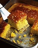 Removing a Piece of Cornbread from the Pan with a Spatula