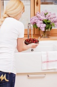 A woman washing cherries in a sink