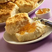 Biscuit with Orange Marmalade on a Plate; Knife; Plate of Biscuits