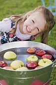 A girl bobbing for apples