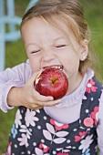 Mädchen beisst in einen Apfel