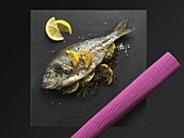 Fried bream with lemons and herbs on a slate plate