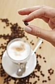 Hand hält eine Kaffeebohne über einem Glas Latte Macchiato