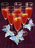 Red cocktail with champagne with butterfly decoration