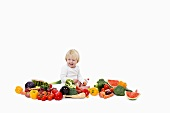 Little child sitting in a the middle of different kinds of colorful vegetables