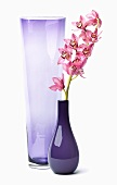 Zwei Vasen aus Glas, eine mit rosa Blumen, weisser Hintergrund