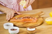 Woman Squeezing a Lemon Wedge over Salmon