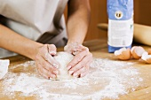 Frau formt Teigkugel auf bemehlter Arbeitsfläche