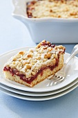 Piece of Cherry Coffee Cake on Stacked White Plates; Fork