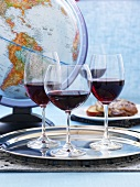 Three glasses red wine on a silver platter in front of a globe