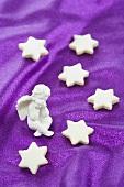 Cinnamon stars and an angel figurine on a purple surface