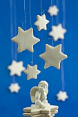 Cinnamon stars hanging above a seated angel figurine