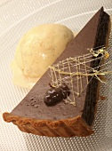 A piece of chocolate tart with vanilla ice cream with caramel decoration