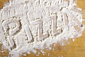 The word 'pizza' written in flour