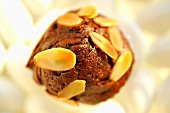 A brownie muffin with slivered almonds