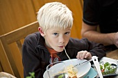 A blond boy eating spaghetti
