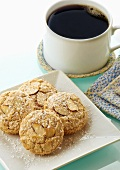 Almond Macaroons Dusted with Powdered Sugar on a White Plate; Cup of Coffee