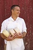 Käsehersteller hält drei Laibe Ziegenkäse