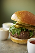 Hamburger with Arugula and Sliced Dill Pickles; Assorted Condiments