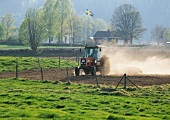 A farmer ploughing a field with a tractor (Sweden)