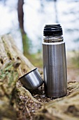 An open Thermos flask on a forest floor