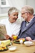Älteres Pärchen in Morgenmänteln beim Frühstück