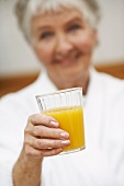 Ältere Frau hält Glas mit Orangensaft
