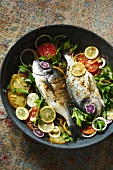 Dorade Fish Cooked in a Skillet with Tomatoes, Lemons and Parsley