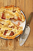 Apple Lattice Crust Pie with Slice Removed; On Wooden Surface with Knife; From Above