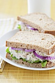 Tuna Salad Sandwich on Whole Wheat Bread with Onion and Lettuce; Halved on a Plate