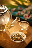 Japanese Genmaicha Tea in a Bowl with Clear Glass Tea Pot and Cup; On Bamboo Tray