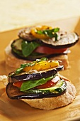 Slices of Bread Topped with Sliced Eggplant, Zucchini, Tomato and Yellow Pepper and Drizzled with Olive Oil