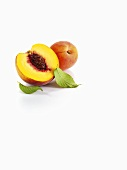 Half a peach and apricots with leaves