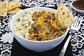 Pumpkin curry with lentils, beans and naan bread (India)