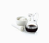 Coarse sea salt in a mortar and a carafe of balsamic vinegar
