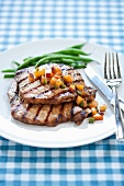 Grilled Pork Chops with Stone Fruit Salsa and Green Beans on a White Plate
