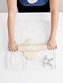 Frau rollt Teig auf einer Marmorplatte aus