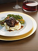 Braised beef ribs on mashed potatoes with chard and red wine