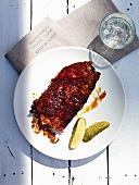Spare ribs with gherkins and a glass of water (seen from above)